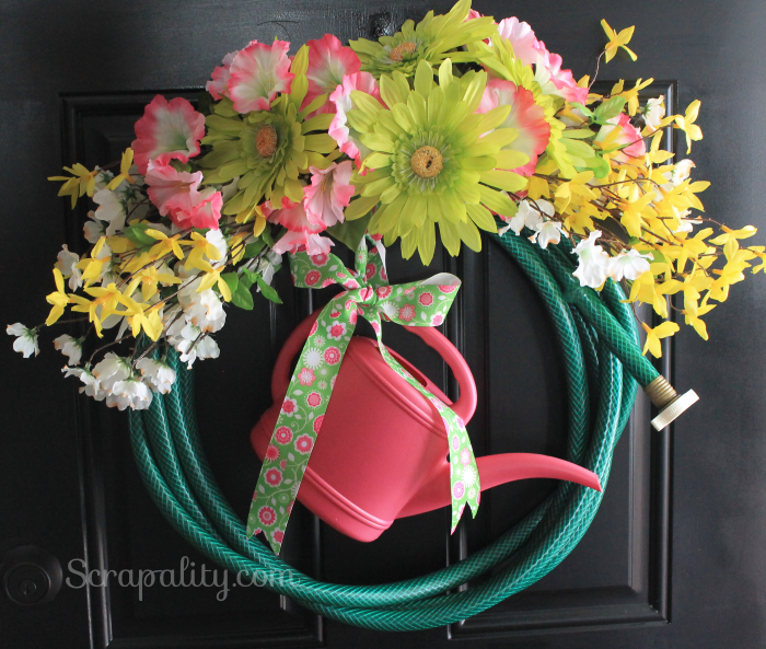 diy garden hose wreath with flowers and watering can